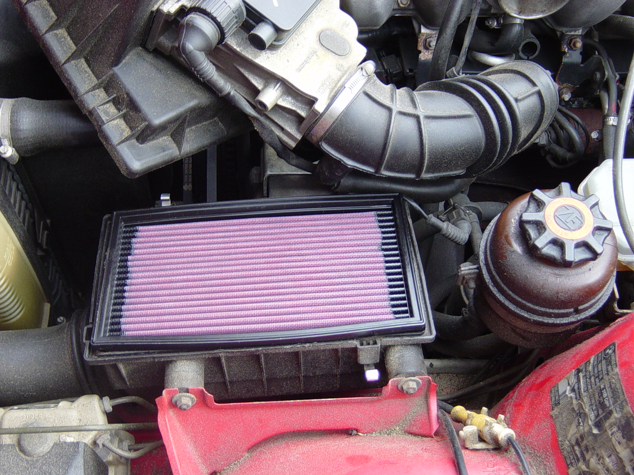 Undo the spring clips that hold the intake muffler top and bottom sections together take out the old air filter install the k n air filter